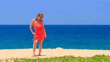 uzun : blond slim girl in short red frock dances on sand beach touches hip and dress wind shakes long hair against azure sea Stok Video