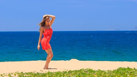 uzun : blond slim girl in short red frock dances barefoot on sand beach and waves hands wind shakes long hair against azure sea Stok Video