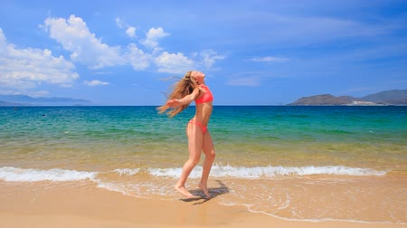 uzun : blonde slim girl in red bikini jumps and does back swings in shallow water on beach against azure sea and sky