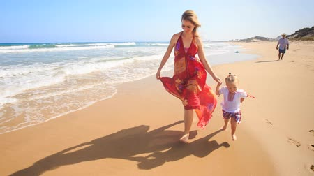 uzun : blond mother in long red dress little girl join hands run along foamy wave surf against azure sea old man at distance