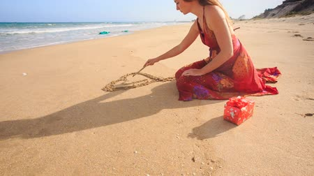 uzun : closeup slim woman in red dress squats draws heart on wet sand at wave surf on beach wind shakes long hair