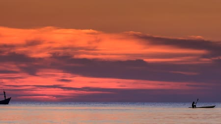 dark bay : silhouettes of boats float along horizon against red clouds in dark sky after sunset