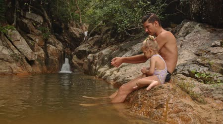 pigtailler : father little blond daughter in swimsuit sit play on stony bank of mountain river with waterfall father shows tricks