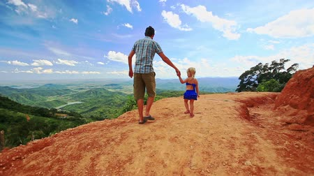 crest dune : caucasian father and little blond daughter walk on sand dune crest against valley landscape and blue sky Stock Footage