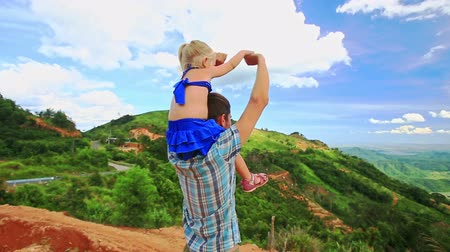 crest dune : closeup backside caucasian father holds little blond daughter on shoulders wave hands against valley landscape blue sky Stock Footage