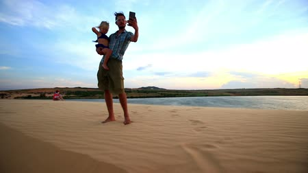 crest dune : caucasian father holds small girl in arms on dune crest makes selfie against lake and blue sky horizon at sunset Stock Footage