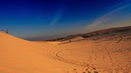 quads : panorama of white sand dunes with tracks distant people jeeps quads motion against blue sky