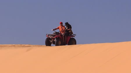 crest dune : MUI NE, BINH THUAN  VIETNAM - MARCH 19, 2016: Tourist and instructor start run down on quad from white sand dune crest on skyline against blue sky on March 19 in Mui ne
