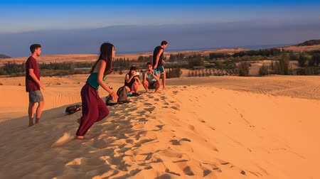 crest dune : MUI NE, BINH THUAN  VIETNAM - MARCH 19, 2016: Tourists guys and girls slide from white sand dune crest against blue sky on March 19 in Mui ne