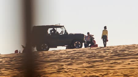 crest dune : MUI NE, BINH THUAN  VIETNAM - MARCH 19, 2016: Jeep drives to tourists on white sand dune crest on skyline against blue sky on March 19 in Mui ne