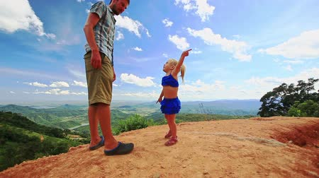 crest dune : Caucasian father little blond girl on sand dune crest girl points sideward against valley blue sky