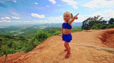 crest dune : Caucasian little blond girl with pigtail stands on sand dune crest points sideward against valley blue sky
