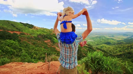 crest dune : Backside view caucasian father holds a little blond daughter on shoulders wave hands against a valley landscape blue sky