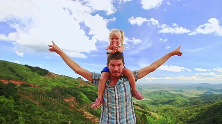 crest dune : Caucasian father holds a little blond daughter on blue background Stock Footage