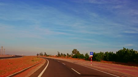 sand lia : camera moves along asphalt road with signs towards infinity among boundless brown sand dunes under blue sky