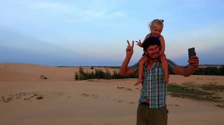 sand lia : closeup caucasian father carries small girl on shoulders both smile show V makes selfie against dunes blue sky at sunset
