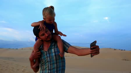 sand lia : closeup father carries small girl on shoulders both smile makes selfie daughter waves hand against dunes sky at sunset Stock Footage