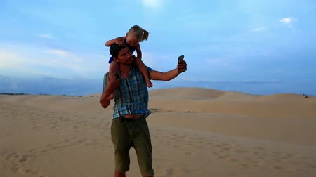sand lia : Closeup father walks carrying small girl on shoulders daughter holding his head against dunes blue sky at sunset