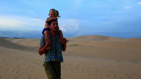 sand lia : Closeup father walks carrying small girl on shoulders daughter waves hands against dunes blue sky at sunset Stock Footage