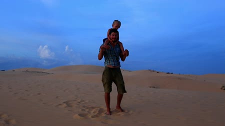 sand lia : father walks carrying small girl on shoulders when daughter laughs and strong wind blows against dunes and blue sky at sunset
