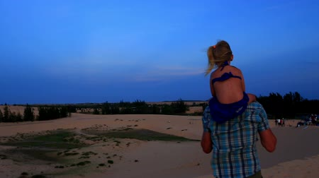 sand lia : Closeup backside father walks with little girl on shoulders strong wind blows against dunes jeeps blue sky at dusk