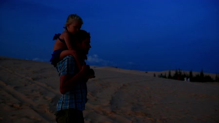 sand lia : closeup father walks holding small girl on shoulders when strong wind blows against dunes and blue sky at dusk