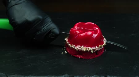 восхитительный : red mousse dessert decorated with coconut shavings and coated with red glaze on black background cuts by knife