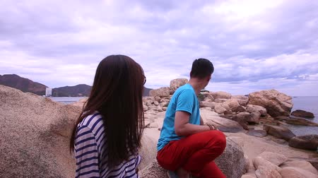 sobre : KHOANG NHA TRANG  VIETNAM - JUNE 20 2015: Vietnamese guy tells a long-haired brunette girl on a large scale in a park at the background of the sea on June 20 in Khoang Nha Trang Stock Footage