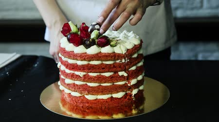 bizet : confectioner hands cut down red decorated cake into two parts Stock Footage