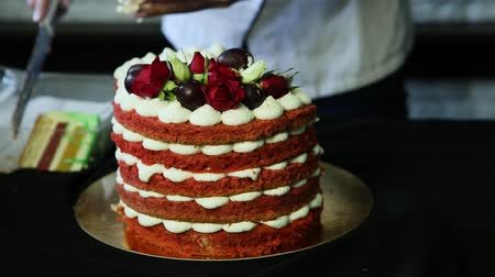 bizet : confectioner hands cut slowly red decorated cake