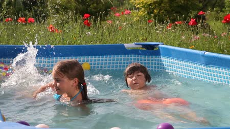 basen : Kids have fun swimming in a pool with nice blue water.