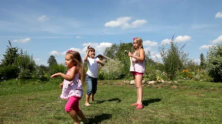 yards : Kids play with soap bubbles outdoor Stock Footage