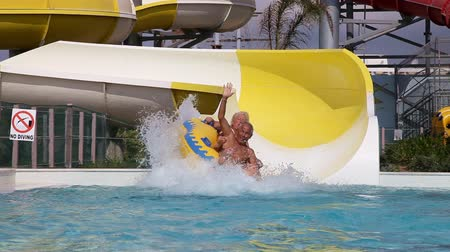 slayt : Senior couple Having Fun On Water Slide Stok Video