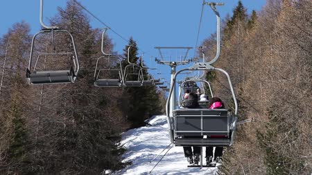 chair lift : Ski lifts with skiers above snow-covered winter forest. Bormio, Italy