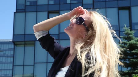 blond vlasy : Portrait of a young woman with wind messing up her hair on a sunny day