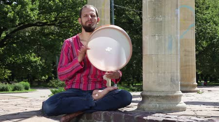 vurmalı : Young man playing the tambourine in a city park on a sunny summer day. Audio included