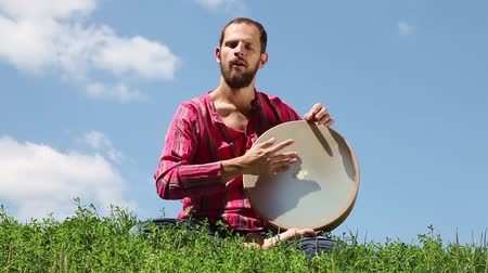 vurmalı : Young man playing the tambourine in front of background of blue sky. Audio included