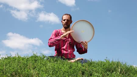 vurmalı : Young man playing the tambourine sitting on the green grass on blue sky background. Audio included