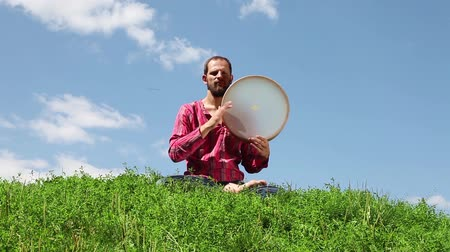 vurmalı : Young man sitting on the green grass and playing the tambourine in front of background of blue sky. Audio included
