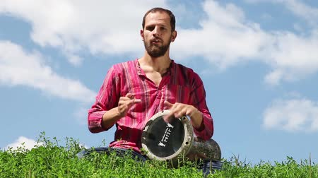 vurmalı : Young Caucasian man sitting on the green grass and playing the drum on blue sky background. Audio included Stok Video