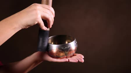 miska : A small Tibetan singing bowl being made to sing in ones hand, close-up