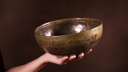 bennszülött : Video shot of Tibetan singing bowl in ones hand in front of brown background. Audio included