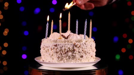 biszkopt : Ones hand lit a candles of the birthday cake in front of black background