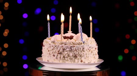 biszkopt : Happy Birthday cake with burning candles rotating in front of black background with flashing lights