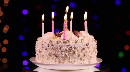doğum günü : Happy Birthday cake with burning candles in front of black background with flashing lights Stok Video
