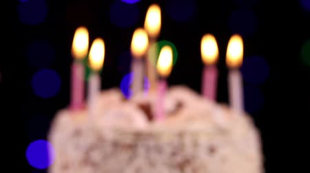 biszkopt : Birthday cake with burning candles appear from blur on black background close-up