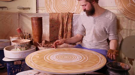 artesão : Craftsman creating a decorative circular panel on a spinning wheel Vídeos