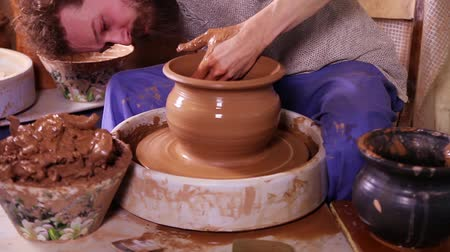készítő : Fast motion video shot of a Potter sculpting a traditional clay pot on a spinning wheel and then crushing it Stock mozgókép