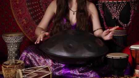 барабаны : Young adult woman playing hand pan during meditation session