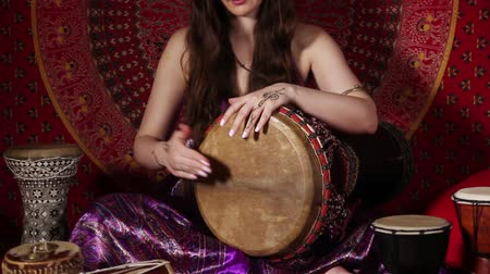 vurmalı : Young Caucasian woman playing drum during meditation session